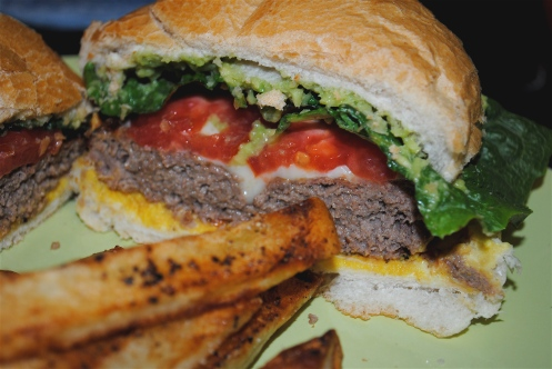grilled hamburger with fries topped with lettuce tomato guacamole Monterey jack cheese