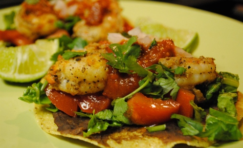 tostada topped with refried beans tomato lettuce shrimp coriander and hot sauce